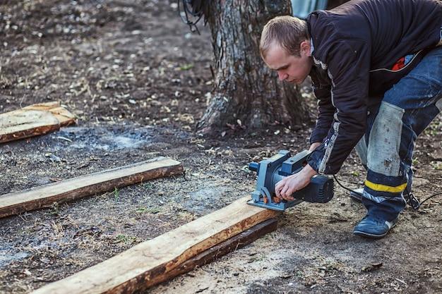 Serra circular para cortar tábuas nas mãos do construtor, o homem viu barras