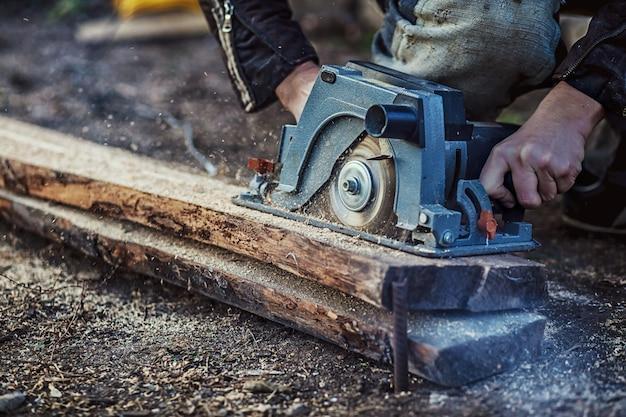 Serra circular para tábuas de corte nas mãos do construtor, da construção e reforma de residências, ferramentas de reparo e construção