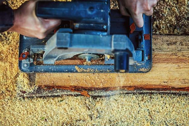 Serra circular para tábuas de corte nas mãos do construtor, o homem serrou barras, ferramentas de construção e reforma de casas, ferramentas de reparo e construção