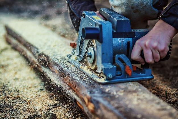 Serra circular para tábuas de corte nas mãos do construtor, o homem viu barras, ferramentas de construção e reforma de casas, ferramentas de reparo e construção