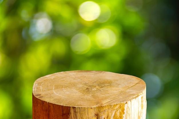 Serra de madeira redonda em formato de cilindro para exposição de produto com fundo abstrato bokeh verde