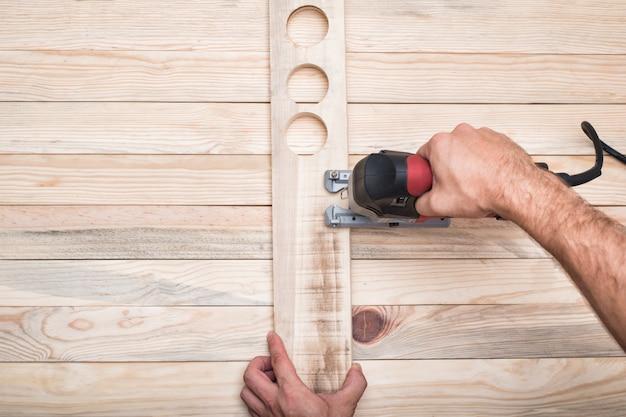 Serra de vaivém elétrica na mão masculina. processamento da peça na mesa de madeira marrom clara. diretamente acima, copie o espaço