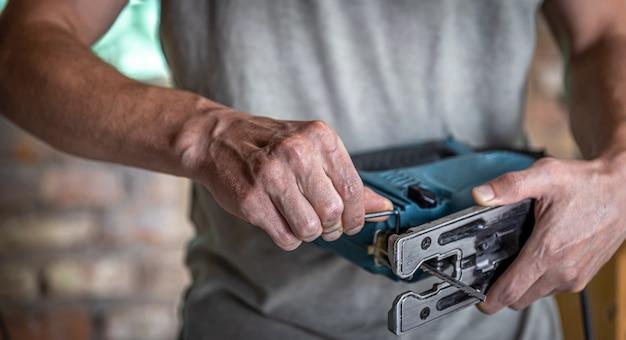 Serra de vaivém elétrico com serra para madeira nas mãos do carpinteiro.