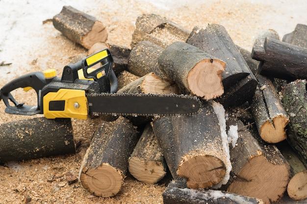 Serra elétrica em toras serradas ao ar livre. ferramenta elétrica para processamento de madeira.