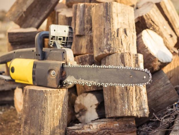 Serra elétrica manual e árvores cortadas para lenha.