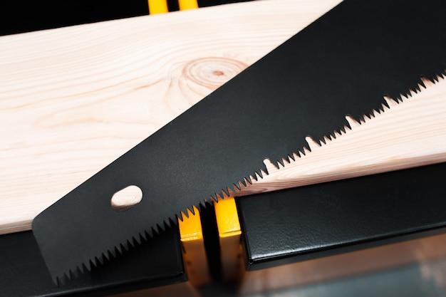 Serra manual em mesa de madeira