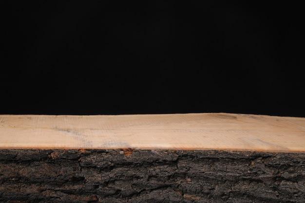 Serrado ao longo de um tronco de árvore com casca em um fundo preto
