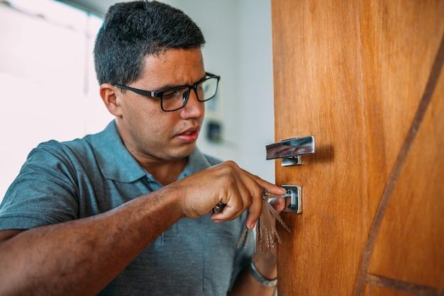 Serralheiro abrindo uma porta as mãos masculinas consertam ou instalam uma fechadura de porta de metal com uma chave de fenda