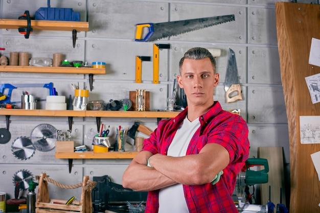 Serralheiro fica na oficina na parede da parede com prateleiras sob as ferramentas