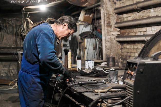 Serralheiro homem idoso processa a peça de trabalho usando uma rebarbadora