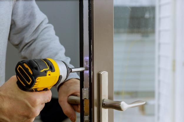 Serralheiro mão segura a chave de fenda na instalação de fechadura