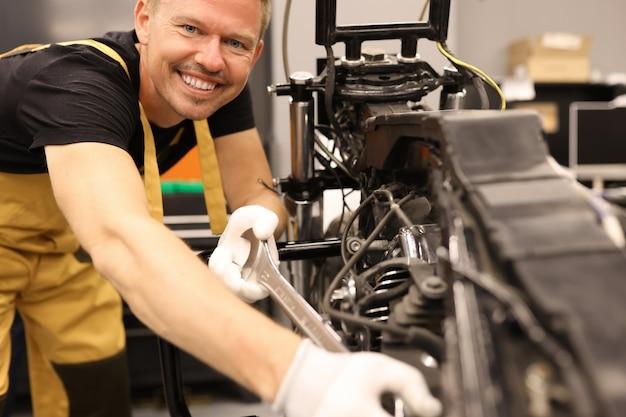 Serralheiro masculino sorridente consertando motocicleta com chave inglesa no centro de serviço de manutenção do motor