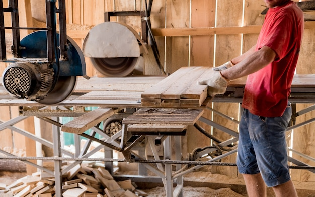 Serraria moderna. um carpinteiro trabalha com madeira para a máquina-ferramenta.