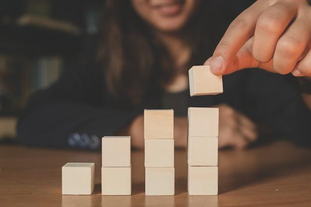 Serviço ao cliente e conceito do apoio - homem de negócios que coloca cubos de madeira com ícones do contato e da comunicação neles na mesa de escritório.