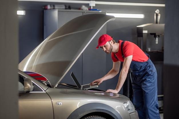 Serviço automotivo. mecânico de automóveis atencioso interessado trabalhando com um laptop perto do capô aberto de um carro em uma oficina mecânica