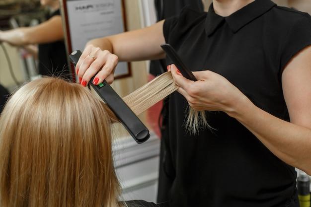 Serviço de cabeleireiro. processo de cortes de cabelo. processo de estilo de cabelo. cabelo mestre mãos com ferro de frisar profissional e pente de perto.