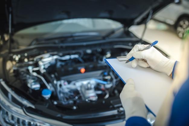 Serviço de carro, reparo, conceito de manutenção - homem asiático mecânico de automóveis ou smith escrevendo para a área de transferência na oficina ou armazém, técnico, fazendo a lista de verificação para a máquina de reparo para um carro novo
