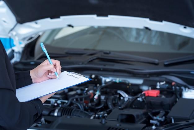 Serviço de carro, reparo, conceito de manutenção - homem mecânico asiático ou smith escrevendo para a área de transferência na oficina ou armazém, técnico, fazendo a lista de verificação para a máquina de reparo para um carro novo
