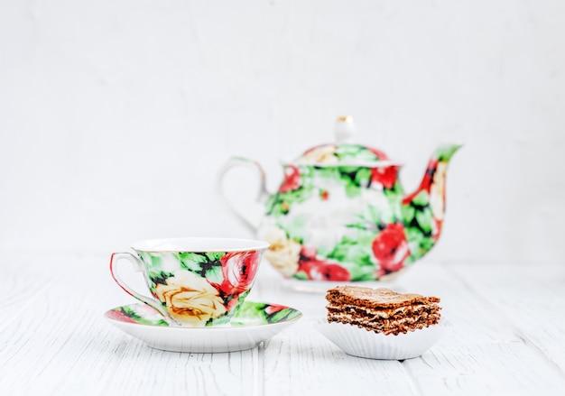 Serviço de chá colorido e bolo em uma mesa de madeira