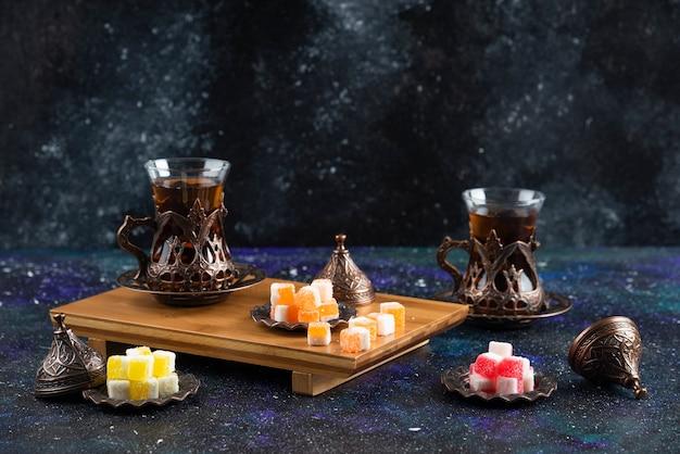 Serviço de chá com delícias turcas em tabuleiro de madeira
