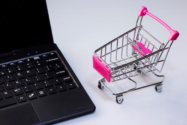Serviço de compras na web on-line. oferece entrega em domicílio. carrinho de compras vazio em um teclado de laptop