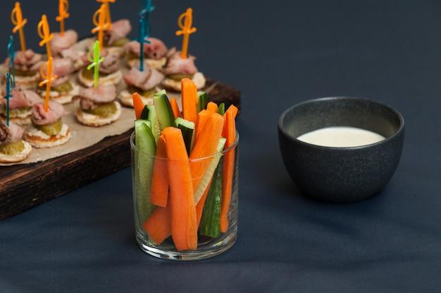Serviço de crudites de vegetais frescos em recipientes de vidro individuais com rodelas de cenoura e pepino com molho de queijo.