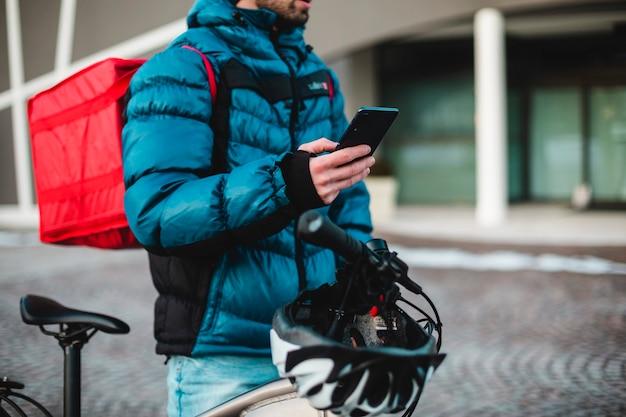 Serviço de entrega de bicicletas de correio em casa. correio do homem usando um aplicativo de mapa no celular para encontrar o endereço de entrega na cidade. alimentos, entrega, correio, bicicleta, 4g