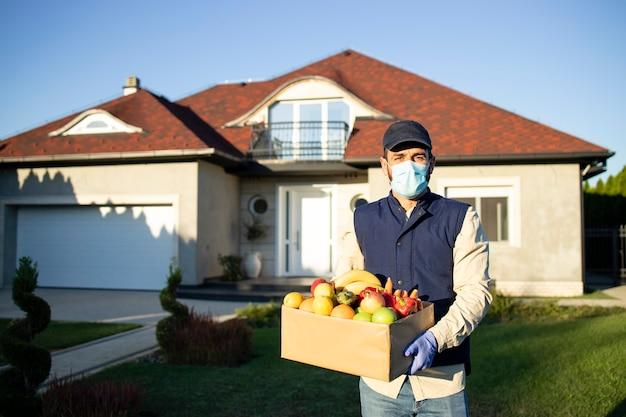 Serviço de entrega de comida durante a pandemia do vírus corona e entregador segurando frutas e vegetais