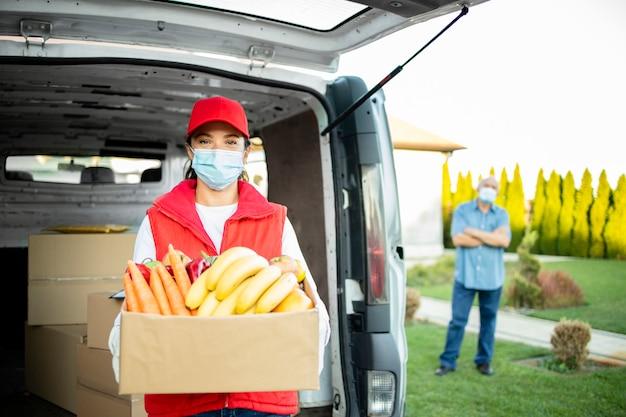 Serviço de entrega de comida durante a pandemia do vírus corona e trabalhador de entrega segurando frutas e vegetais