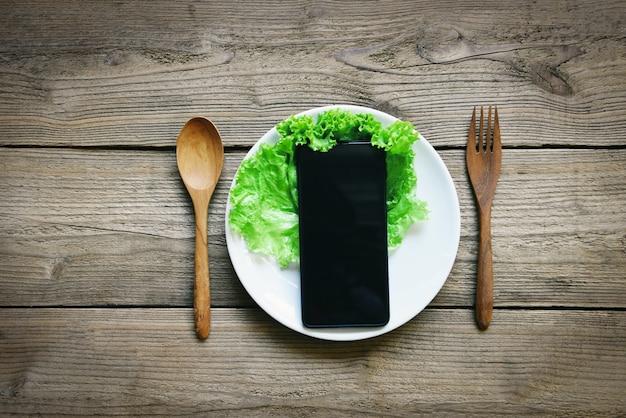 Serviço de entrega de comida pedido on-line telefone inteligente deitado no prato conceito de pedido de comida