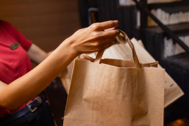 Serviço de entrega de correio em casa. a mensageira entregou a encomenda sem um saco com o nome da comida.