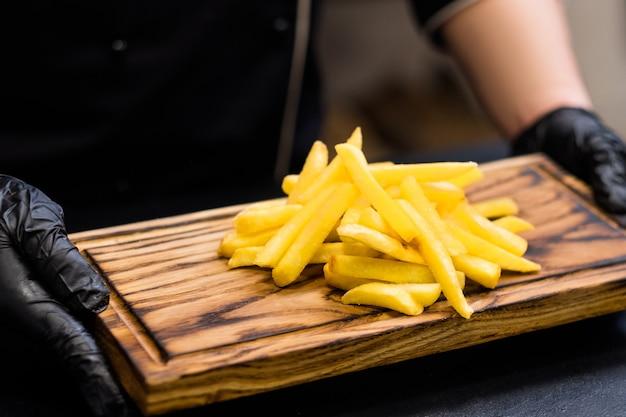 Serviço de entrega de fast food. foto recortada do chef segurando batatas fritas salgadas na placa de madeira rústica.