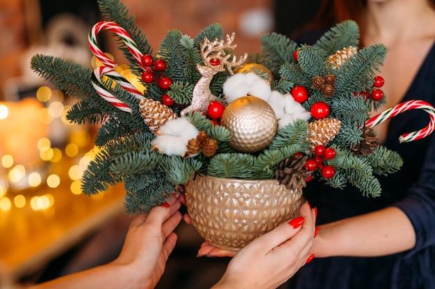 Serviço de entrega de loja de souvenirs florística. close up da panela com árvore do abeto, bastões de doces, veados, arranjo de bolas de natal.