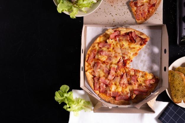 Serviço de entrega de pizza em uma caixa de papelão com pão de queijo de alho