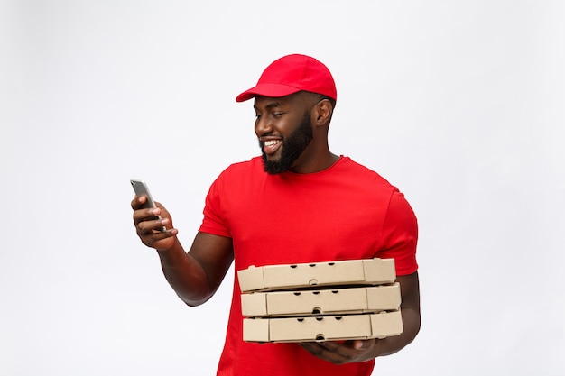 Serviço de entrega: entregador de pizza africano bonito falando ao celular com expressão facial feliz.
