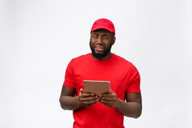 Serviço de entrega - retrato de homem afro-americano sério entregador com tablet em expressão agressiva boba e infeliz.