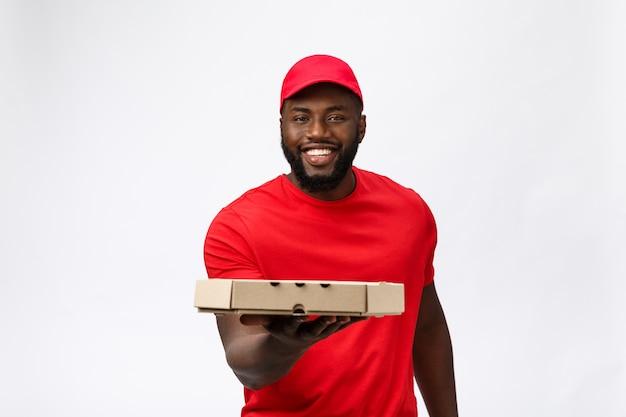 Serviço de entrega - retrato de um homem bonito afro-americano entregador de pizza.