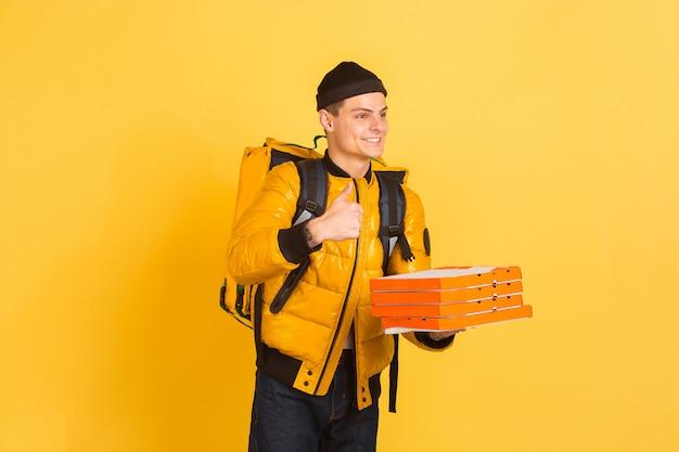 Serviço de entrega sem contato durante a quarentena. homem entrega comida e sacolas de compras durante o isolamento. emoções de entregador isolado em amarelo