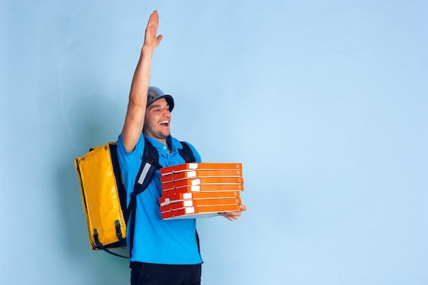 Serviço de entrega sem contato durante a quarentena. homem entrega comida e sacolas de compras durante o isolamento. emoções do entregador isoladas em azul