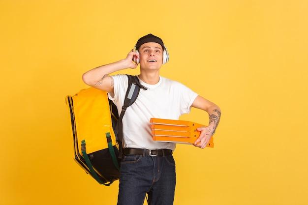 Serviço de entrega sem contato durante a quarentena. o homem entrega comida e sacolas de compras durante as emoções de isolamento do entregador isolado na parede amarela