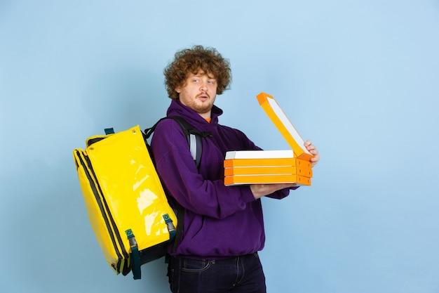 Serviço de entrega sem contato durante a quarentena. o homem entrega comida e sacolas de compras durante as emoções de isolamento do entregador isolado na parede azul