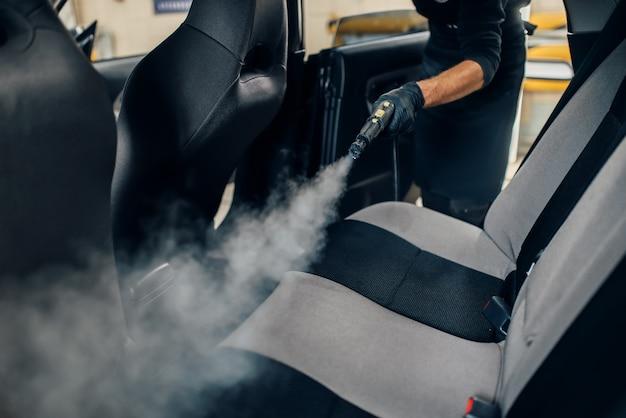 Serviço de lavagem de carros, trabalhador do sexo masculino com luvas limpa assentos com limpador a vapor. limpeza a seco profissional do interior do carro