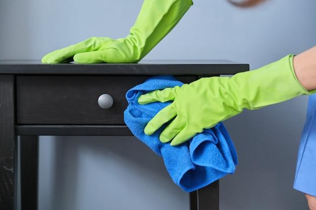Serviço de limpeza, close-up das mãos enluvadas com pano de microfibra para limpar a poeira, limpeza de apartamento