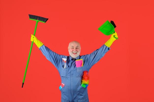 Serviço de limpeza homem sorridente de uniforme com equipamento de limpeza profissional de serviço doméstico