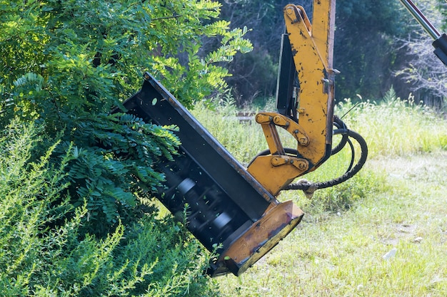 Serviço de manutenção de estradas em rodovias suburbanas de segadeira de máquina de mecanização de trator, corte de grama, equipamento de corte externo montado destacável dirigindo na beira da estrada