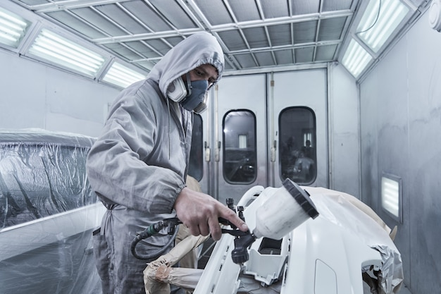 Serviço de pintura e reparação de automóveis. mecânico de automóveis de macacão branco pinta o carro com pulverizador aerógrafo na câmara de pintura
