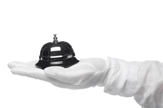 Serviço de primeira classe. mão nas luvas brancas, segurando o sino do hotel