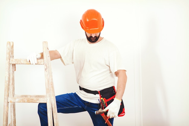 Serviço de reformas domésticas. homem de pintor no trabalho. trabalhador manual com um cinto de ferramentas.
