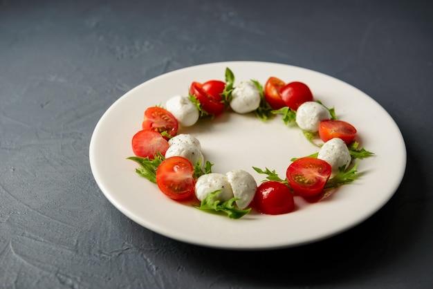 Serviço de restaurante de deliciosa e saudável salada caprese na chapa branca