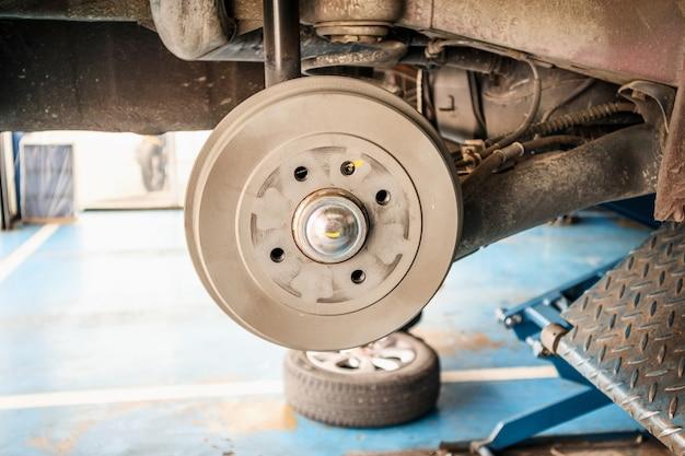 Serviço de troca de pneus, freio de carro sem rodas em oficina mecânica